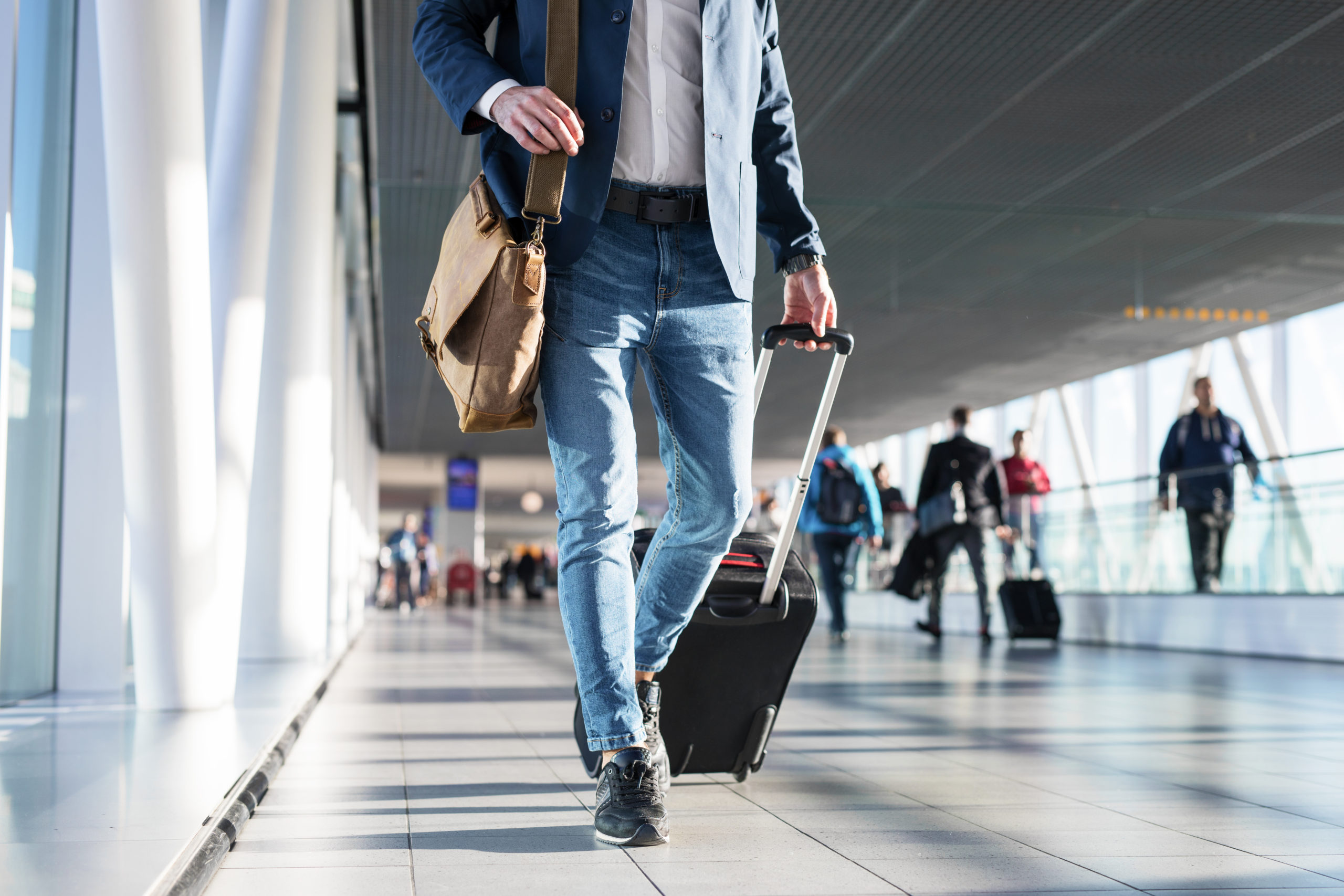 Man,With,Shoulder,Bag,And,Hand,Luggage,Walking,In,Airport